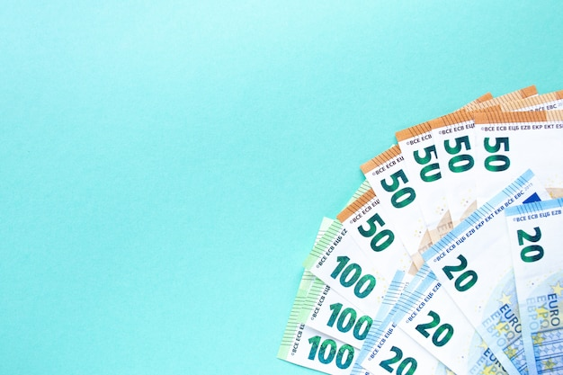 青色の背景。左隅が100、50、20ユーロの紙幣。お金と金融の概念。テキストのための場所。