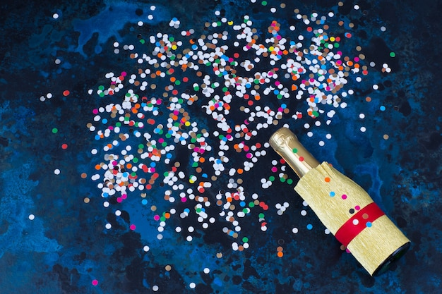On blue background a bottle of champagne and bright confetti