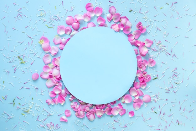 Blue background decorated with fresh flower petals