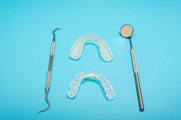 치과 aligner와 마운트 부목, 복사 공간 치과 클리닉에 대 한 파란색 배경.