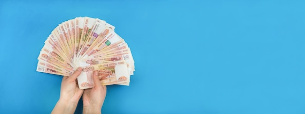 On a blue background, the girl's hands, in which she holds the russian currency close-up.