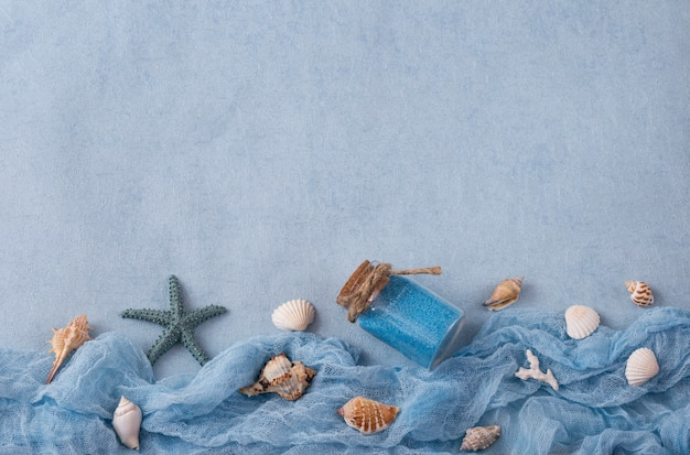 On a blue background, objects with marine themes: seashells, sea sand and a starfish