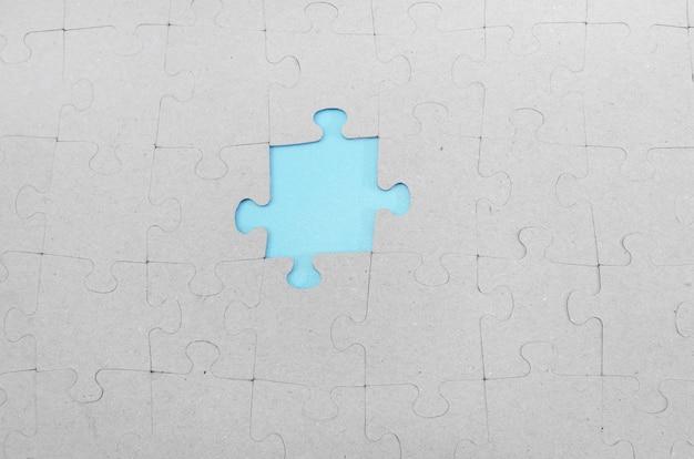 灰色のパズルの欠けている部分を通して輝く青い背景