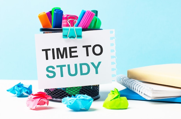 On a blue background - a stand with bright markers, notepads and multi-colored crumpled pieces of paper. a sheet of paper with the text time to study.