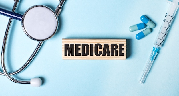 On a blue background, a stethoscope, a syringe and pills and a wooden block with the word medicare. medical concept