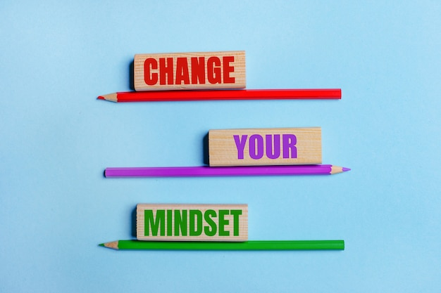 On a blue background, three colored pencils, three wooden blocks with text change your mindset