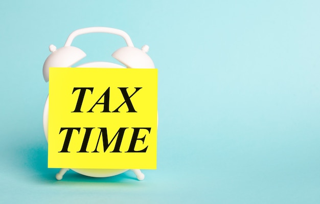 On a blue background - a white alarm clock with a yellow sticker for notes with the text tax time.
