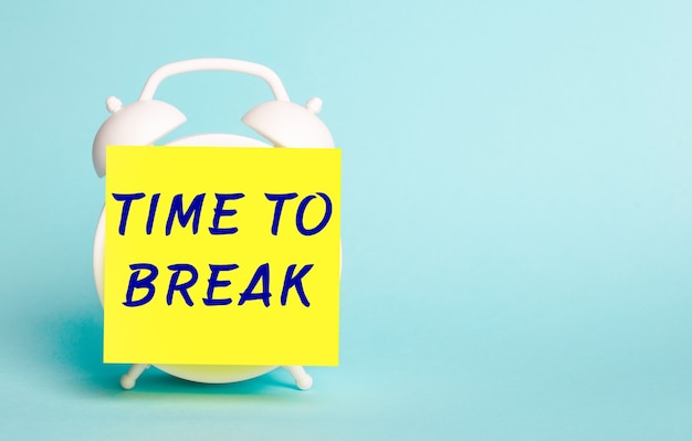 On a blue background - a white alarm clock with a yellow sticker for notes with the text time to break.