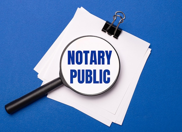 On a blue background, white sheets under a black paper clip and on them a magnifying glass with the text notary public
