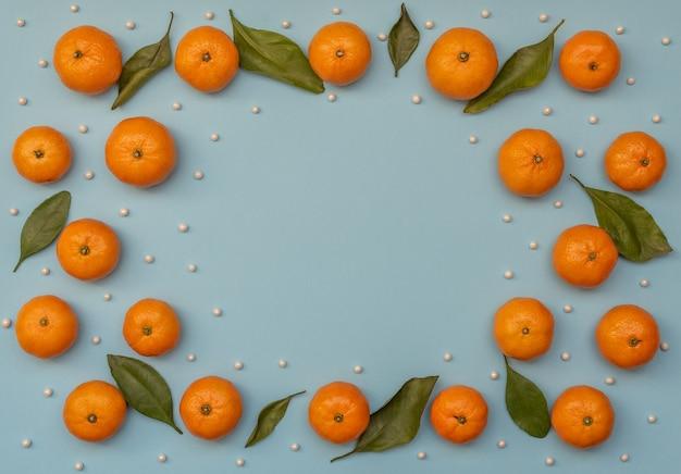 녹색 나뭇잎과 눈처럼 흰 구슬 오렌지 감귤과 파란색 배경. 크리스마스 인사말 카드입니다. 플랫 레이 스타일.