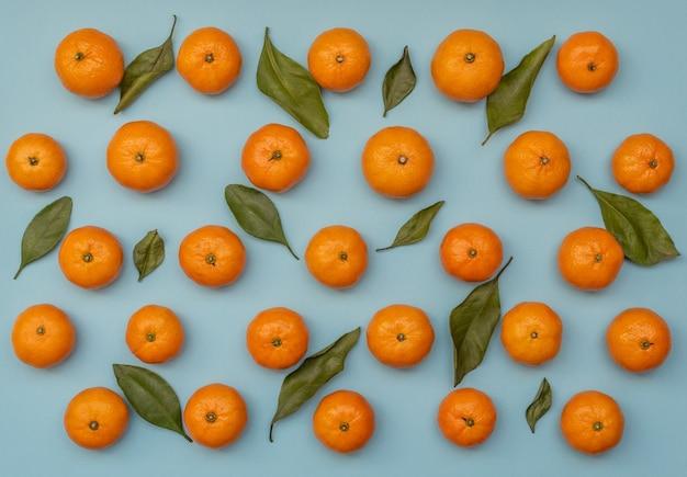 Синий фон с оранжевыми мандаринами с зелеными листьями. плоский стиль.