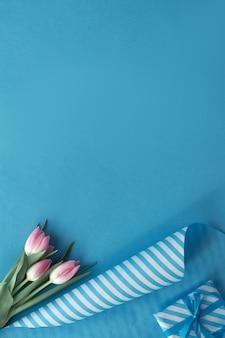 Синий фон с розовыми тюльпанами, полосатой упаковочной бумагой и подарочными коробками, копией пространства