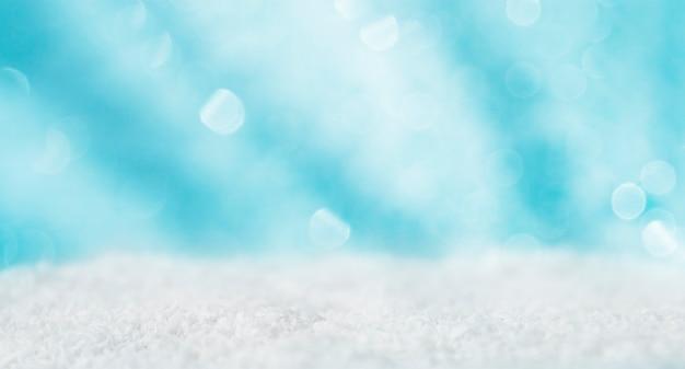 雪と焦点ぼけライトと青い背景