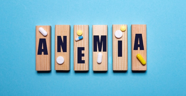 On a blue background, wooden blocks with the word anemia and pills. medical concept