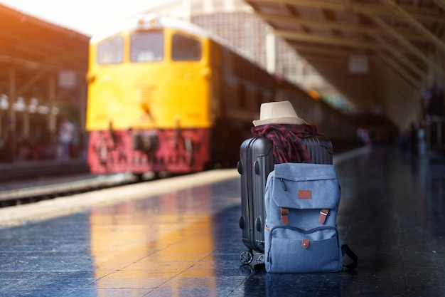 荷物に帽子をかぶった青いバックパックとスコットシャツ、駅の旅行者用スーツケース。旅行と休暇のコンセプト。
