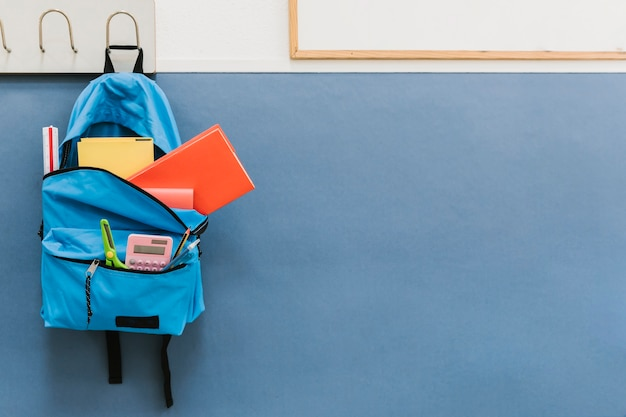 Blue backpack on hook in school