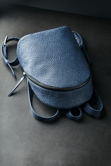 Blue backpack made of genuine leather on dark