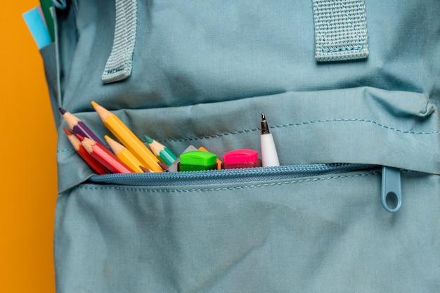 Синий рюкзак с разными красочными канцелярскими принадлежностями на желтом
