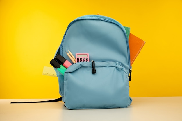 Blue backpack with different colorful stationery on table back to school
