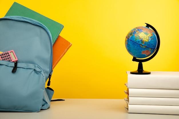 Синий рюкзак со школьными принадлежностями с глобусом на книгах обратно в школу