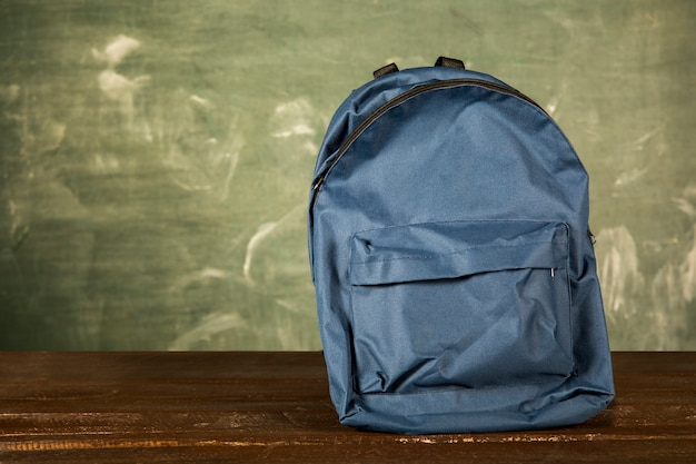 Blue backpack on wooden table