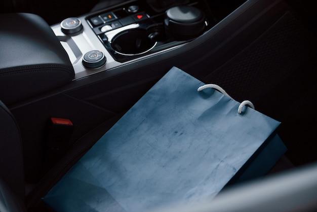 車で横になっている青いバッグ。ブランドの新しいモダンな高級車のインテリアのクローズアップ表示