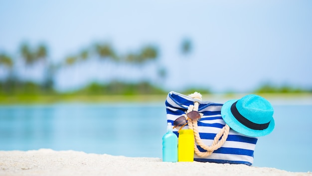 Blue bag, straw hat, sunglasses and sunscreen bottles on white beach