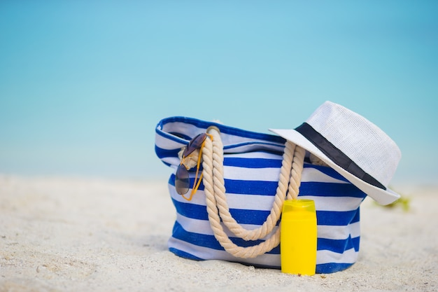 Blue bag, straw white hat, sunglasses and sunscreen bottle on tropical beach