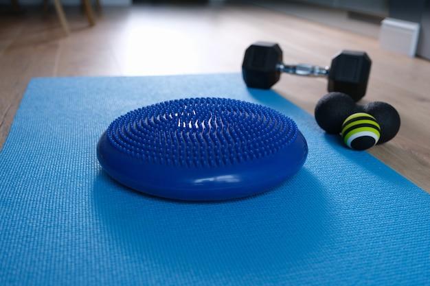 Blue balance cushion lying on mat near dumbbells and roll ball home closeup