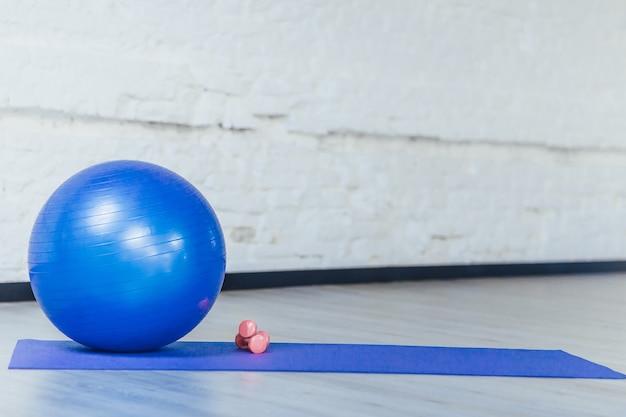 Синий мяч и гантели в тренажерном зале
