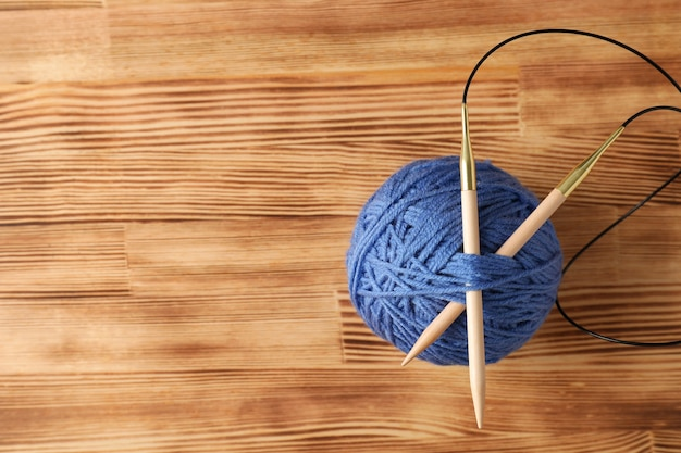 軽い木製のテーブルに編み針が付いた青い毛糸のボール。