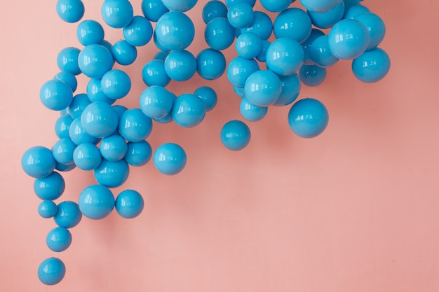 Blue balloons, blue bubbles on pink background. modern punchy pastel colors