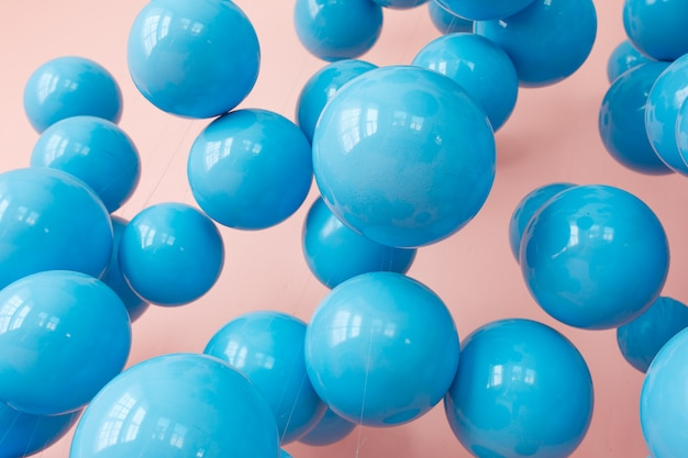 Blue balloons, blue bubbles on pink background. modern punchy pastel colors.