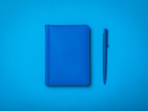Синяя шариковая ручка и синий блокнот на синем фоне. монохромное изображение офисных принадлежностей.
