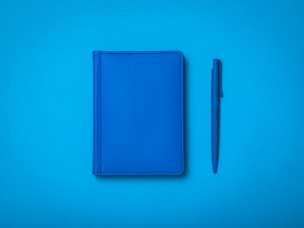 Blue ballpoint pen and blue notepad on a blue background. monochrome image of office accessories.