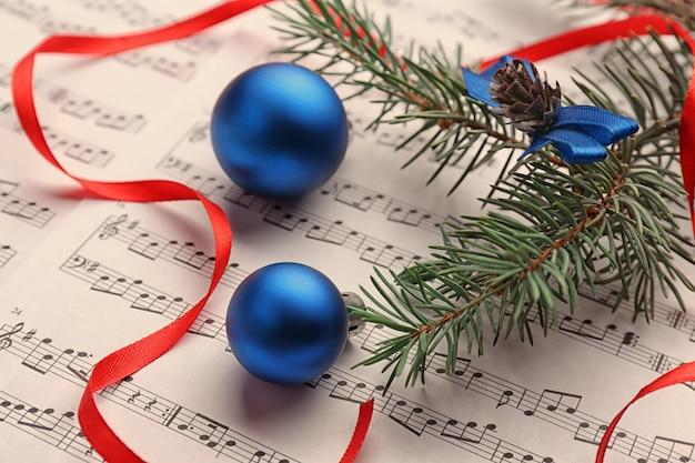 Синие шары на нотном листе. концепция рождественских песен