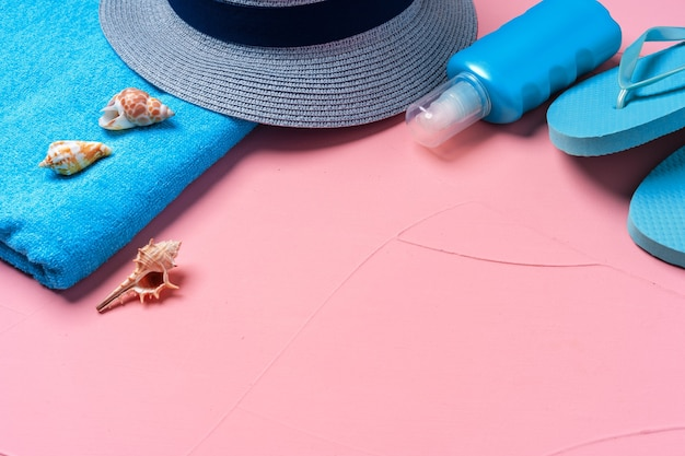 Blue beach accessories with seashells on pink, flat lay