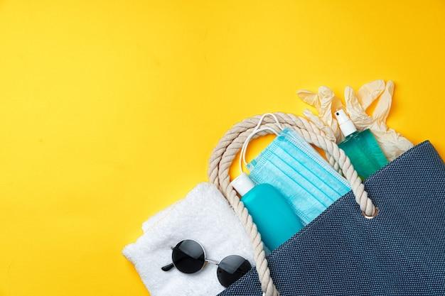 黄色の背景にビーチアクセサリーと保護マスクが付いた青いビーチバッグ