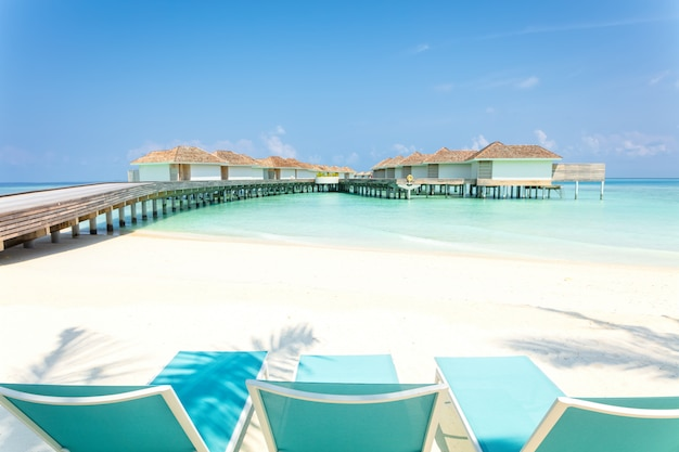 Blue beach chairs on white sand with wooden jetty and tropical villas in maldives on background, tropical holiday.