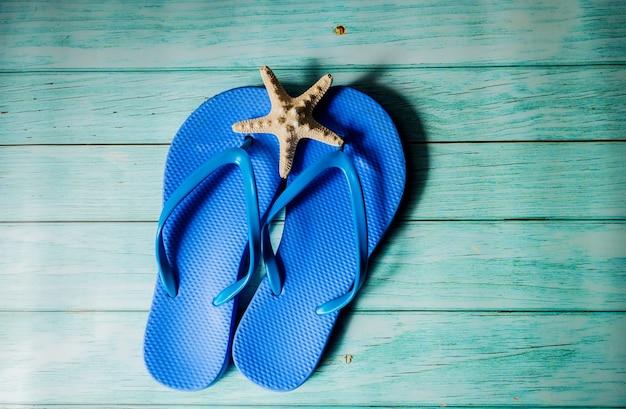 青い木の床に青いビーチスリッパ。上面図。夏休み