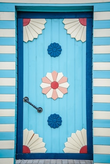 Blue beautiful plank door with patterns in the wooden fence