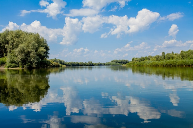 Blue beautiful sky against the river. clouds are displayed in calm water. on the horizon, the green bank of the dniester, place for fishing