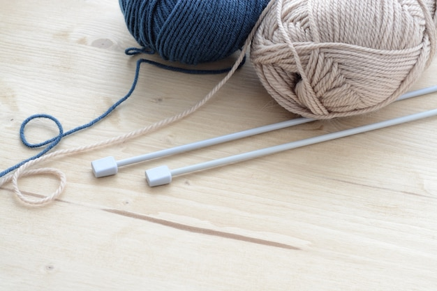 Blue and beige knitting yarn clews with needles on wooden table