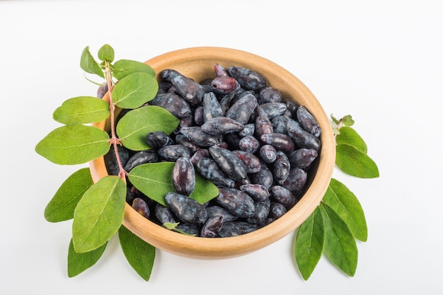 흰색 배경에 잎이 있는 갈색 그릇에 블루 베리