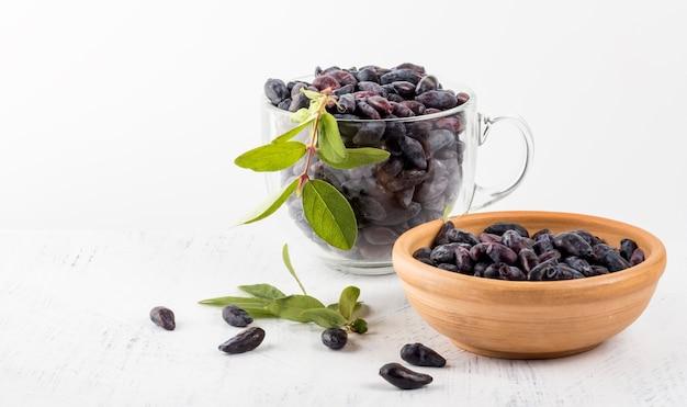 유리 컵에 든 블루 베리와 흰색 배경에 나뭇잎이 있는 갈색 그릇