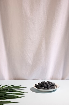 Blue berries on plate with palm leaf on table against white curtain