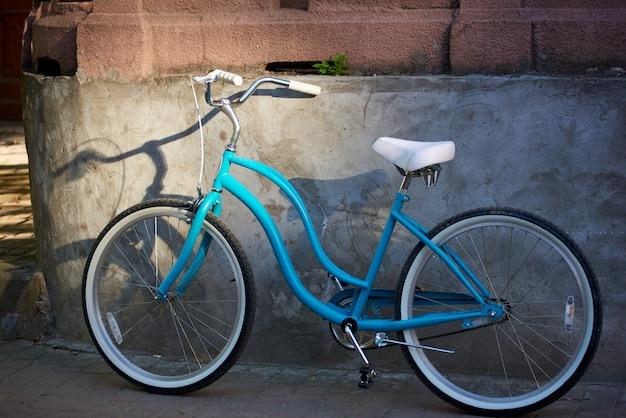 市内中心部の建物の壁の近くの青い自転車