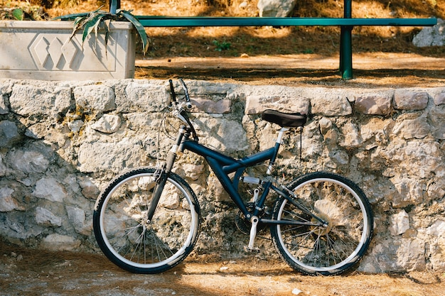 通りの石の縁石のそばの青い自転車