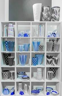 Vasi di fiori in ceramica blu, nera e bianca su uno scaffale