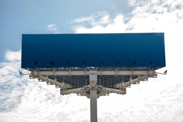 Blue blank hoarding against sky